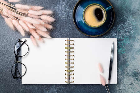Open white blank notebook, coffee cup, pink dried flowers bouquet on desk of home office flat lay. Freelance, blogging, feminine, working concept top view, copy space Foto de archivo