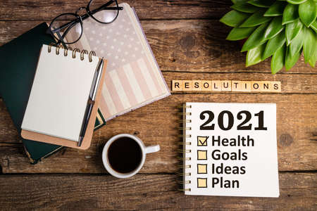 New year resolutions 2021 list. Office desk table with notebooks, coffee cup, succulent, american flag. Goal, plan, ideas, business, motivation, health concept
