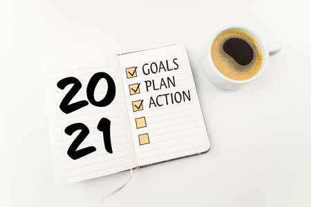 New year goals 2021 on desk. 2021 resolutions list with notebook, coffee cup on white desk. Resolutions, plan, goals, action, checklist, idea concept. New Year 2021 template, copy space