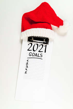 New year goals 2021 on desk. 2021 resolutions with notebook and santa hat on white background. Goals, plan, strategy, change, idea concept. Copy space Foto de archivo