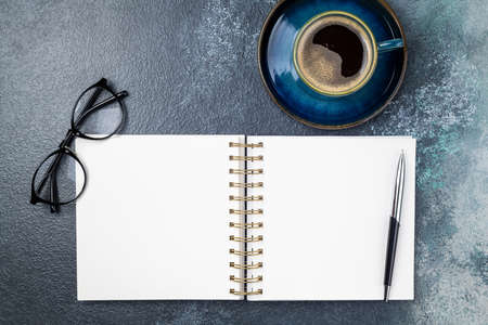 White blank notebook, coffee cup, eyeglasses on desk of home office flat lay. Freelance, blogging, business, working concept. Top view with copy space, flat lay