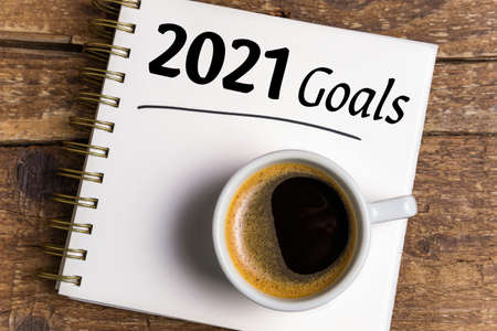 New year goals 2021 on desk. 2021 goals list with notebook, coffee cup on wooden background. Goals, plan, strategy, business, idea, action concept. Top view Foto de archivo