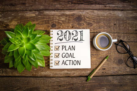 New year goals 2021 on desk. 2021 resolutions list with notebook, coffee cup and eyeglasses on wooden background. Goals, plan, strategy, business, idea, action concept, top view