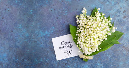 Notes good morning and bouquet of flowers lily of the valley on blue background. Good day, breakfast, greeting card, gift concept. Flat lay. Top view