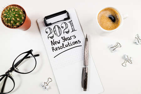 New year resolutions 2021 on desk. 2021 goals list with notebook, coffee cup and eyeglasses on white desk. Goals, plan, strategy, resolutions, business, idea concept