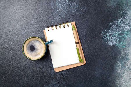 White blank notepad and coffee cup on office table. Flat lay desk with business accessories open notepad and cup of coffee. Copy space, top view