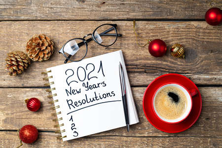 New year 2021 resolutions on desk. 2021 goals with notebook, coffee cup, eyeglasses, Christmas ornaments on wooden background. Goals, plan, strategy, action, idea concept