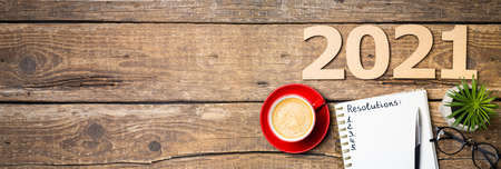 New year resolutions 2021 on desk. 2021 resolutions with notebook, coffee cup, succulent, eyeglasses on wooden background. Goals, plan, strategy, list, idea concept. New Year 2021 template with copy space