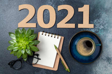 New year resolutions 2021 on desk. 2021 goals with open notebook, coffee cup, eyeglasses, plant succulent on blue background. Goals, plan, strategy, action, idea concept. New Year 2021 template with copy space