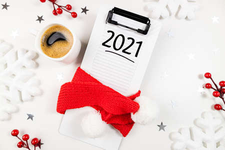 New year goals 2021 on desk. 2021 resolutions list with notebook, coffee on white desk. Goals, plan, resolutions, strategy, change, idea concept. Copy space, flat lay