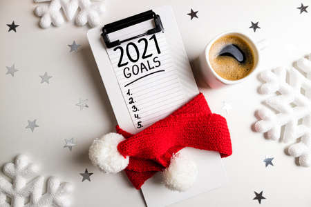 New year goals 2021 on desk. 2021 goals list with notebook, cup of coffee, decorations on white. Goals, plan, resolutions, strategy, idea concept