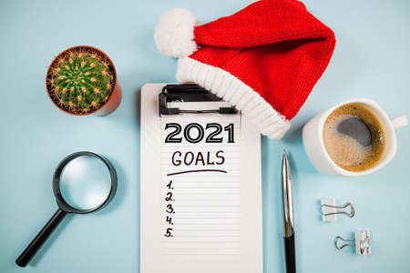 Top view 2021 goals list with notebook and coffee cup on blue desk. 2021 resolutions, goal, plan, strategy, business, idea concept