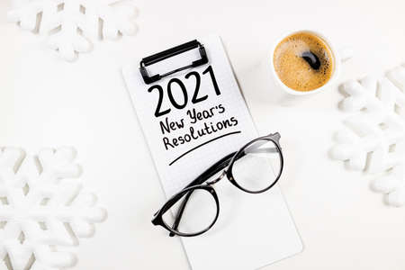 New year goals 2021 on desk. 2021 goals list with notebook, coffee cup and eyeglasses on white table. Resolutions, plan, goals, action, idea concept. New Year 2021 template, copy space