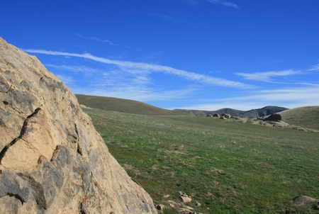 Sandstone geology, green field and blue sky in Wind Wolves Preserve, Bakersfield, CA
