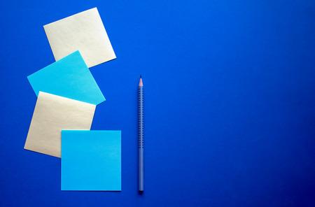 Des stikers carrés bleus et jaunes disposés avec un crayon argenté sur le fond bleu foncé. Banque d'images
