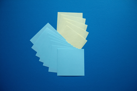 Many blue and yellow square stikers arranged on the dark blue background. Archivio Fotografico