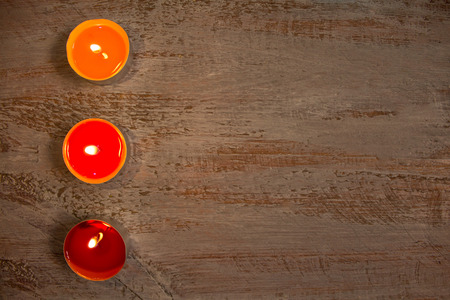 Beautiful colorful candles on the painted wooden boards. Standard-Bild