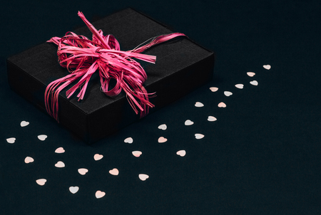 Vintage black gift box with pink ribbon bow on black background sprinkled with heart shaped confetti. Copy space. Stock fotó