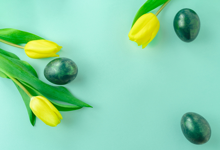 Beautiful spring concept with Easter eggs and yellow tulips on turquiose blue background. Flat lay. Copy space.