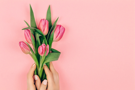 Trendy delicate spring manicure. Female hands with nail design on pink background holding pink tulip flowers. Copy space.