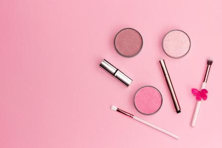 Composición laicos plana con productos de maquillaje decorativos sobre fondo rosa pastel. Copie el espacio.