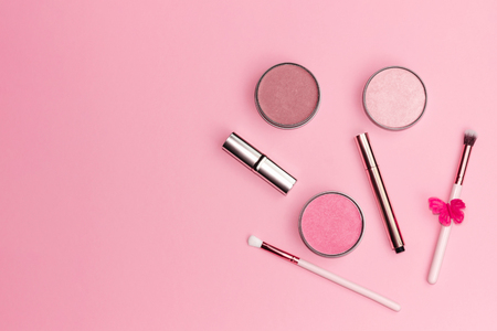 Flat lay composition with decorative makeup products on pastel pink background. Copy space.
