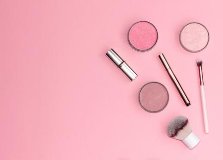 Flache Zusammensetzung mit dekorativen Make-up-Produkten auf pastellrosa Hintergrund. Platz kopieren.