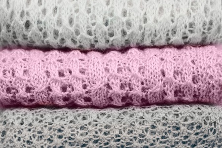 Stylish knitted pastel colored sweaters and one in sweet lilac trendy color of spring and summer 2019. Knitwear clothing with clearly visible texture. Close up, copy space.