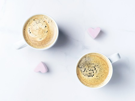 Romantic desk top with two cups of coffee and pink heart shaped marshmallows. Top view. Copy space.