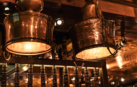 Two beautiful brass vintage lamps in a cafe with vintage wooden interior. Banque d'images