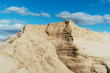 Industrial sand quarry. Sand pit. Construction industry. Sand hill agains the blue sky. 版權商用圖片