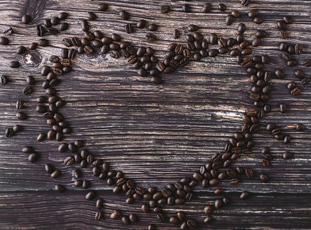 Heart shaped frame made of spilled coffee beans on a wooden table. Rustic stile. Top view.