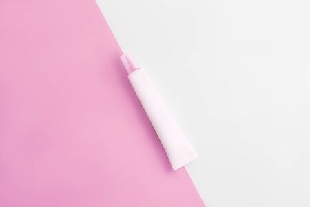 Cosmetics tube on pastel pink and white background. Copy space. Flat lay. Beauty industry concept.