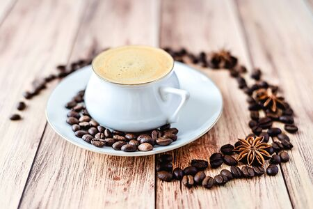 Close-up view of a cup of hot coffee on wooden rustic table with spilled coffee beans and anise. Space for text .