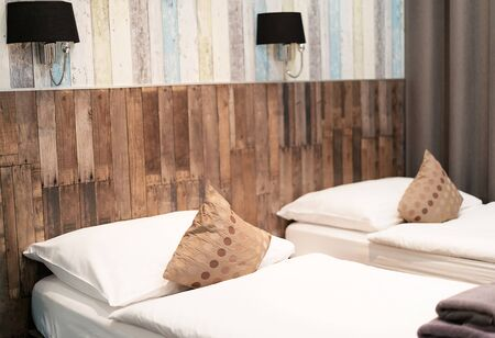 Hotel room with two beds along a striped wooden wall at night.