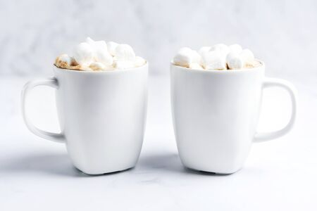 Romantic cozy desk top with two cups of coffee with marshmallows on marble table. Close-up. Space for text .