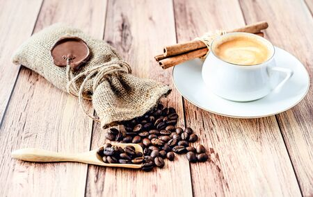 Cup of hot coffee, cinnamon sticks and coffee beans in a wooden scoop and spilling out from a hessian bag on wooden rustic table. Close-up. Stockfoto