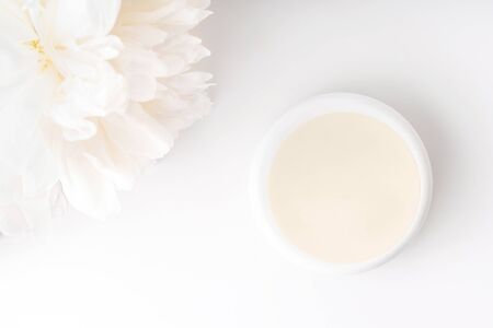 White peony and mockup face and body cream on white background. Cosmetics concept. Flat lay.