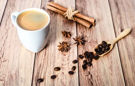 Cup of hot coffee, cinnamon sticks and coffee beans spilling out from a wooden scoop on wooden rustic table. Close-up.
