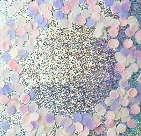 Frame of pastel colored confetti on shiny holographic background. Festive backdrop.