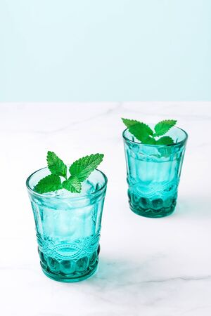 Two beautiful vintage turquoise glasses with cold drink and ice cubes, decorated with fresh green mint leaves on white marble table. Close-up.
