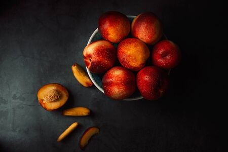 Still life of fresh delicious sweet nectarines with droplets of water in a bowl on dark background. Low key. Top view.