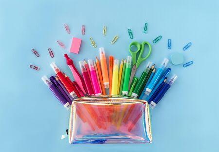 Zurück zum Schulhintergrund mit geöffnetem trendigem Neon-Federmäppchen mit verschiedenen Schulmaterialien in Regenbogenfarben auf pastellblauem Hintergrund Flach liegen. Nahansicht. Platz kopieren.