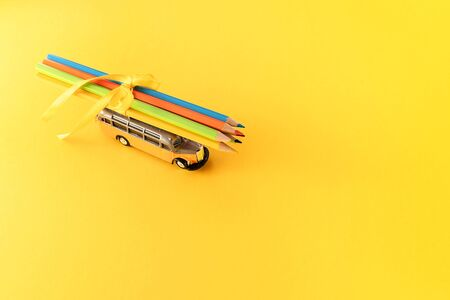 Toy school bus with variety of colorful pencils tied with yellow silk ribbon on bright yellow backdrop. Back to school concept. Website banner.