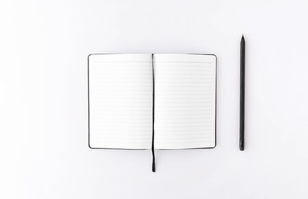 Top view of opened notepad with black pencil white background. Mockup for your design. Flat lay. Фото со стока