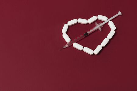 White pills in a shape of heart with a syringe with red liquid on red background. Flat lay style. Copy space. Medicine, healthcare and pharmacy concept.