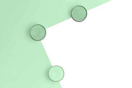 Eyeshadows in different shades of mint on trendy mint and isolated white background. Flat lay. Copy space. Stock Photo