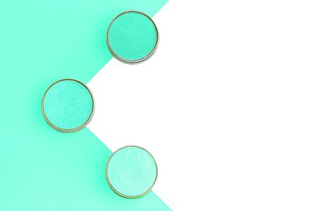 Eyeshadows in different shades of mint on trendy mint and isolated white background. Flat lay. Copy space.
