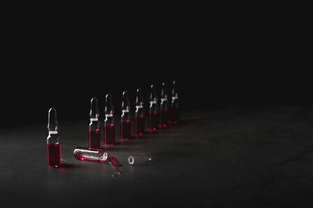 Row of ampules for injections with red liquid on dark background. Medicine, healthcare and pharmacy concept. Low key photo. Imagens