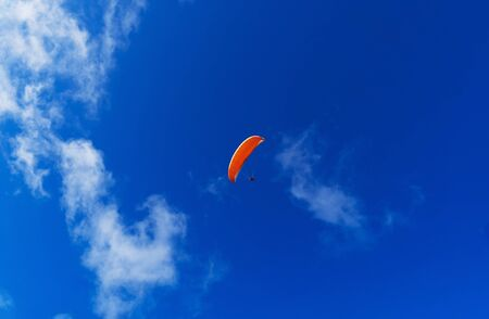 Paraglider flying over the mountains on a bright summer day. Paragliding sport concept. Copy space.